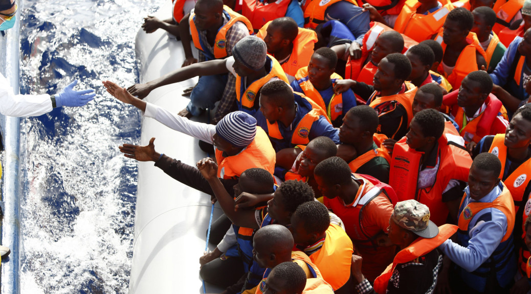 A group of 104 sub-Saharan Africans on board a rubber dinghy prepare to board the NGO Migrant Offshore Aid Station (MOAS) ship Phoenix some 25 miles off the Libyan coast in this handout photo provided by MOAS October 4, 2014. MOAS, a privately-funded humanitarian initiative, began operating at the end of August and has assisted in the rescue of some 2,200 migrants crossing from Libyan shores towards Europe.   REUTERS/MOAS/Darrin Zammit Lupi/Handout via Reuters (MID SEA - Tags: SOCIETY IMMIGRATION) MALTA OUT. NO COMMERCIAL OR EDITORIAL SALES IN MALTA - RTR48XT1
